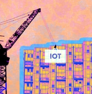 """Graphic of commercial building construction with a crane lifting up a block that says """"IoT"""""""