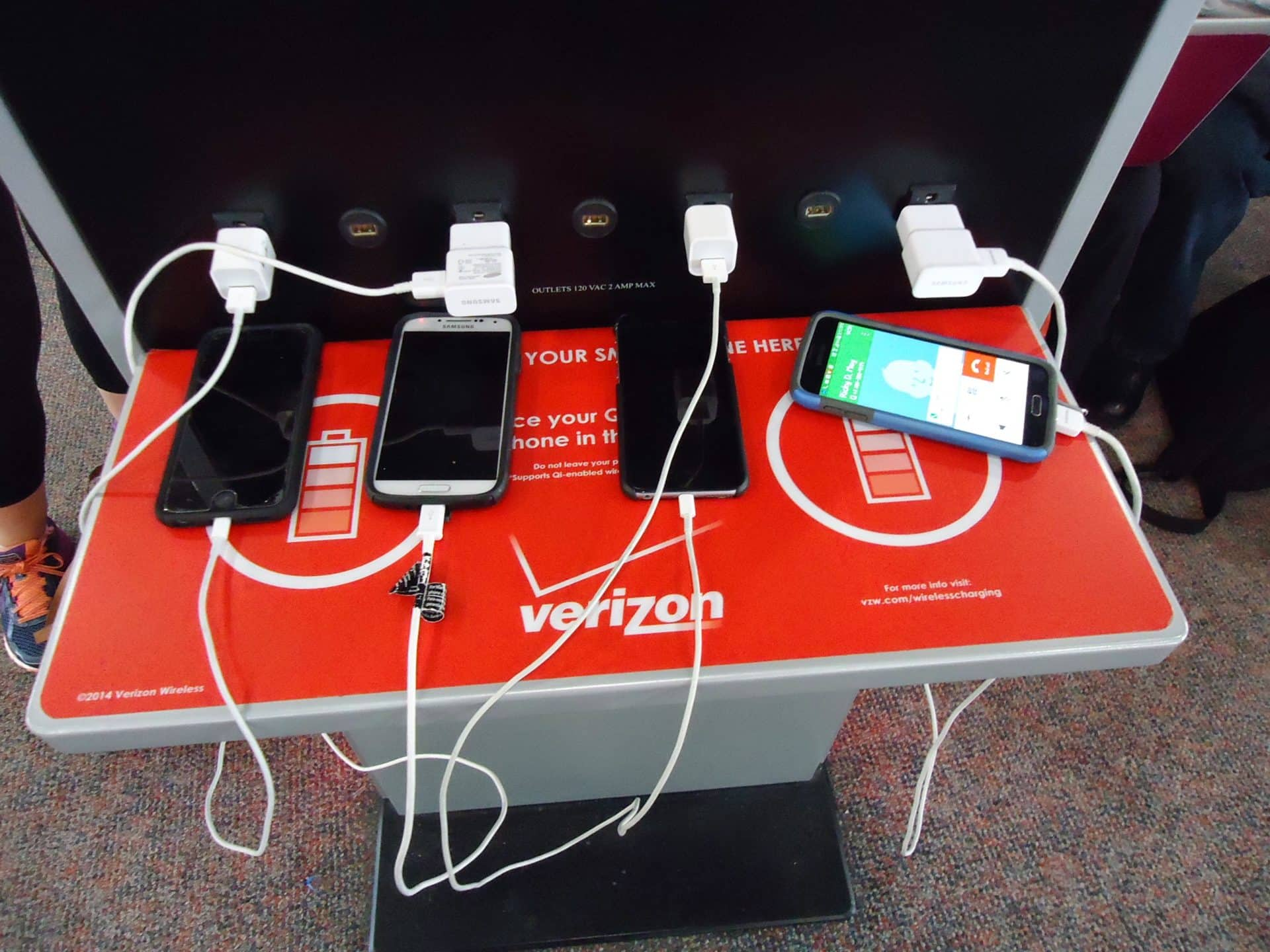 Phones are being charged with cables and plugs in an airport lounge