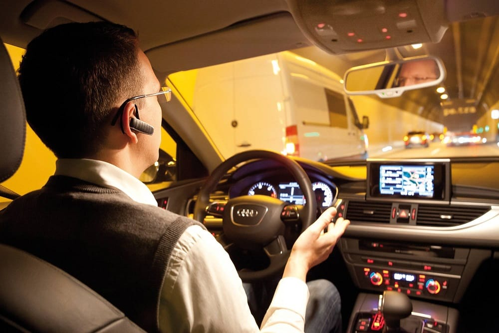 A man sits in an autonomous car in a tunnel without touching the steering wheel