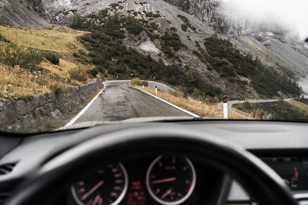 A sporty vehicle is being driven down a winding road in the mountains