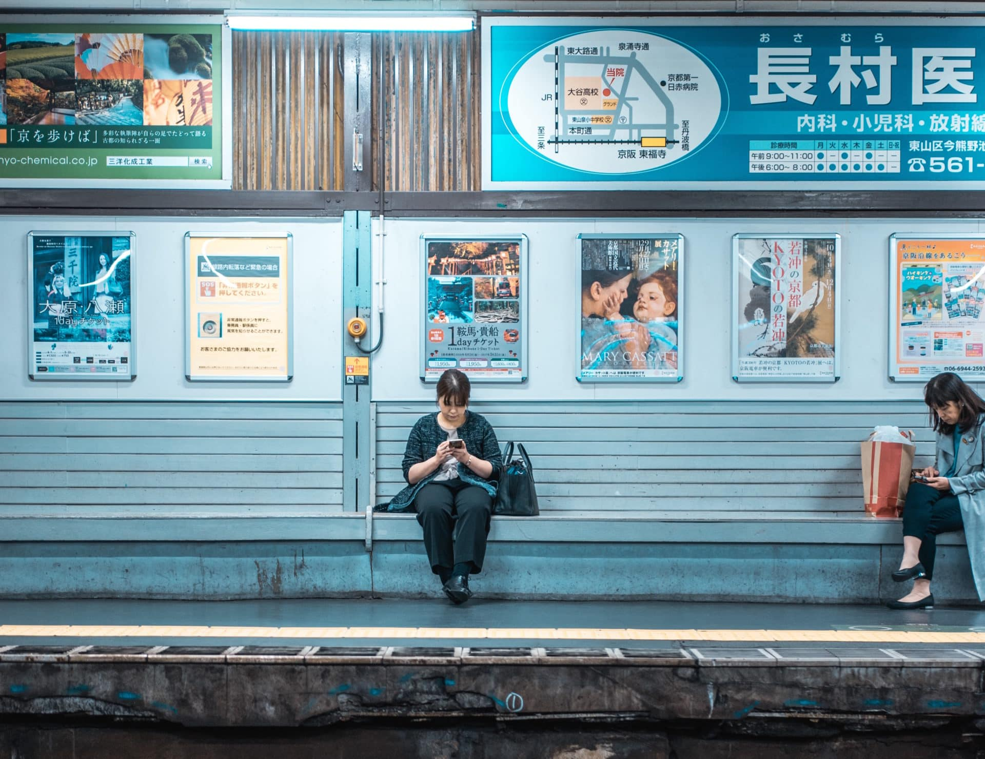 A person sitting on a bench at a train station in Japan.