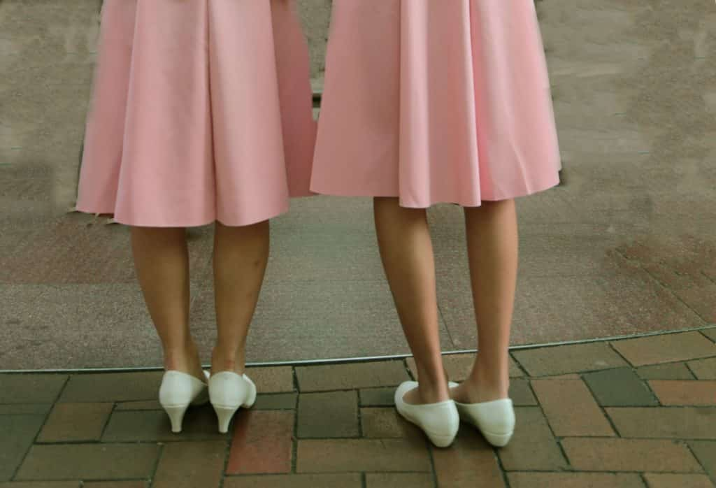Two women's legs with pink skirts and white shoes.