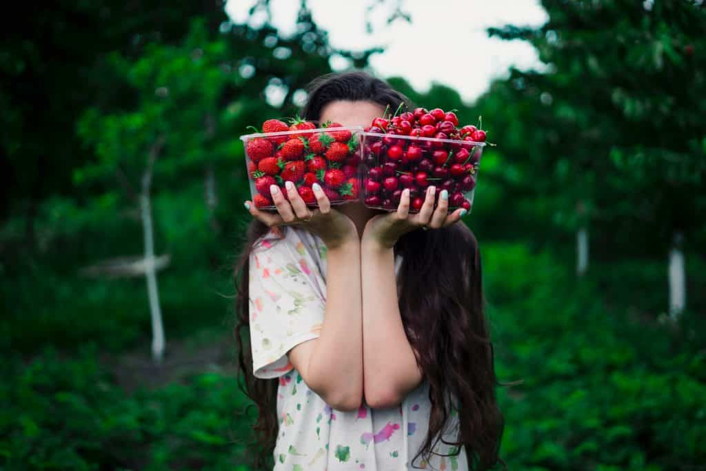 someone holding a punnet of strawberries and a punnet of cherries