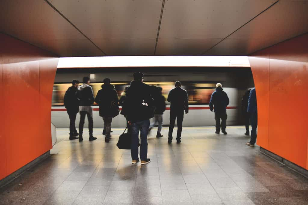 People wait on a metro platform as a train passes