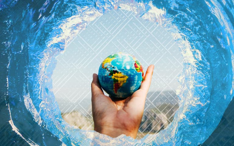 A hand holding up a tiny globe