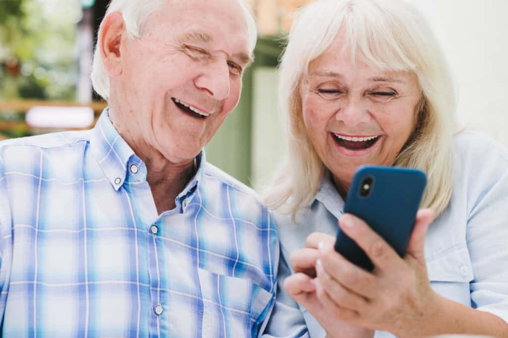 An elderly man and woman look at a smartphone and laugh