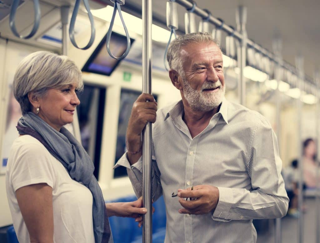An older couple stand in a subway train