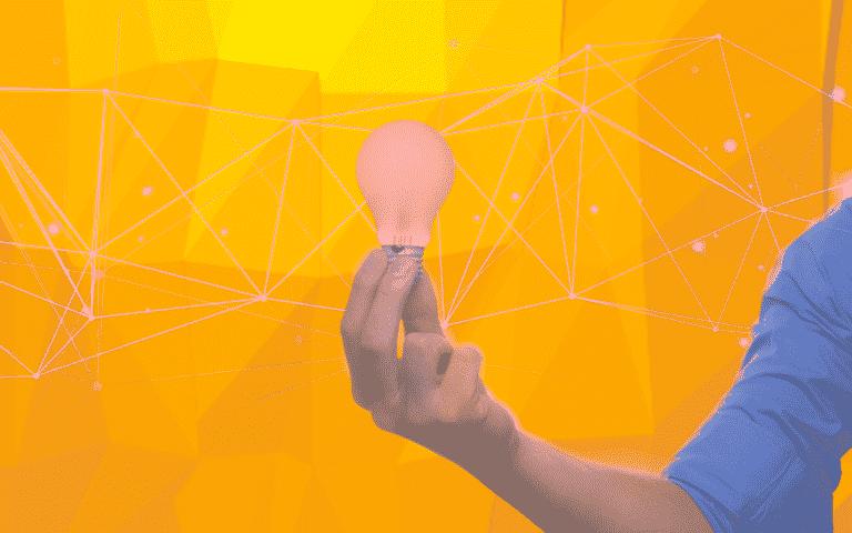 A hand holding a smart lightbulb