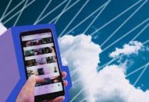 A hand holding a smart phone in front of clouds